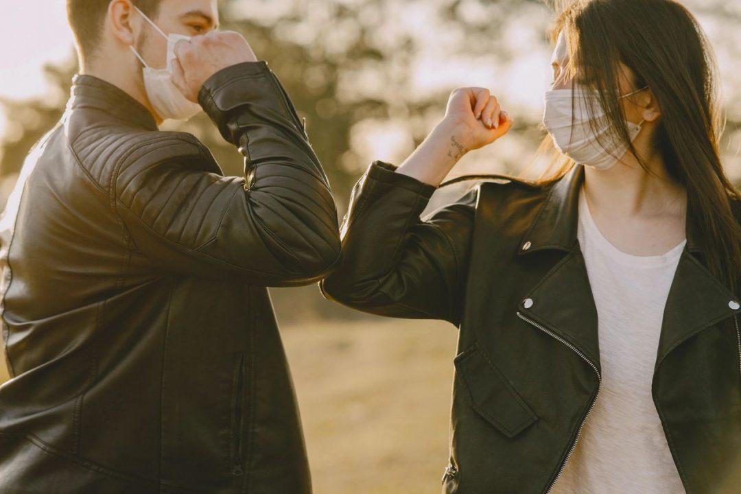 Man and woman wearing masks touching elbows