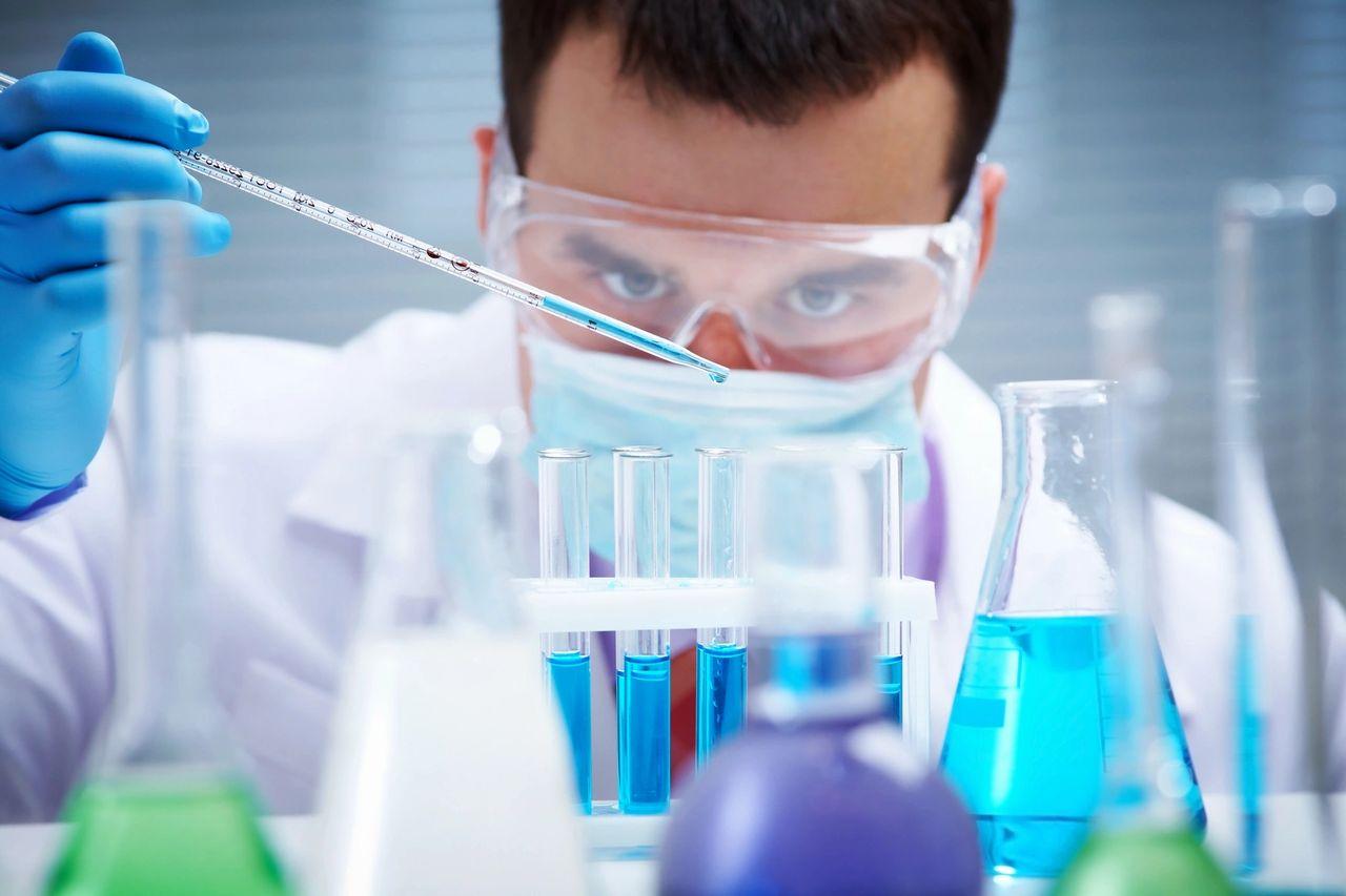 Lab worker measuring liquid in test tubes